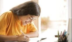 Smiling student doing homework in front of laptop